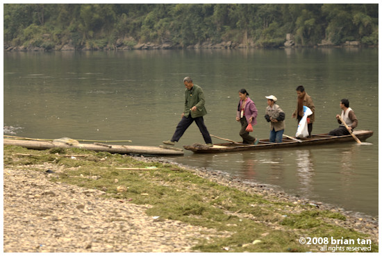 Locals crossing the river using small slim boats