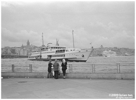 Locals (I guess) looking at a passenger Bosphorus ferry, Galata tower in the far background...
