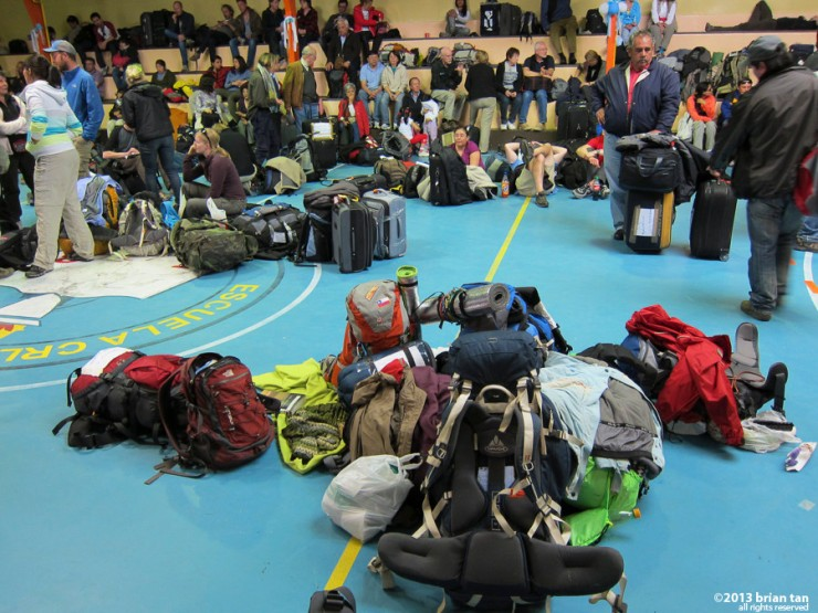 Bags, people in the school gymnasium converted into a tourist sorting centre