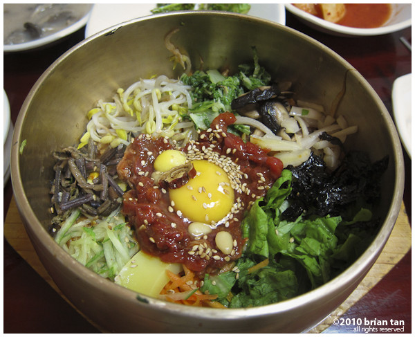 Bibimbap before mixing. The red stuff is the beef. Gochujang is already mixed into the rice under all the toppings.