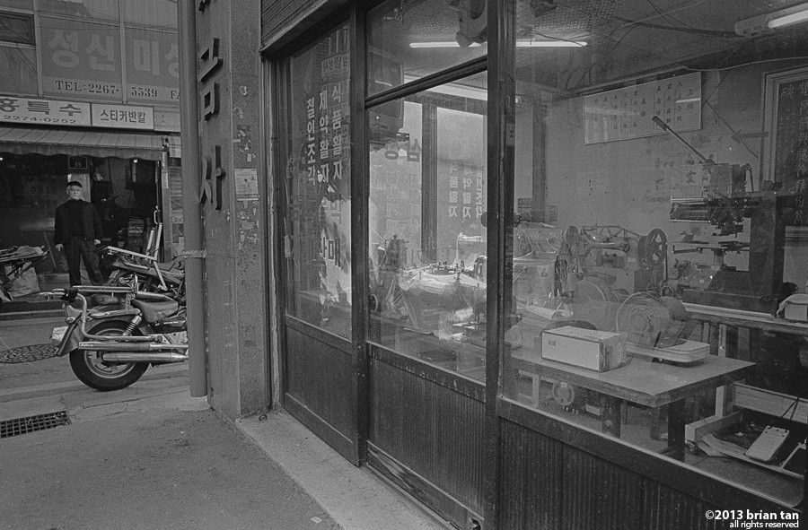 Walking into the small alleys, here's the first workshop, sewing machines. It took me some time to meter this show, trying to balance the strong backlighting with the shadows inside the shop. And this is the reason I prefer film, you can control the contrast by development and prevent blown highlights.